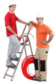 Two electricians with copper coil and ladder — Stock Photo