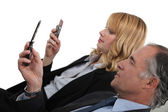 Moss and employee checking e-mails on their mobiles — Stock Photo