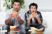 Father and son sat on the sofa eating burgers — Stock Photo