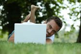 Man using his laptop on a lawn — Stock Photo