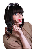 Woman wearing glasses and holding multiple sunglasses — Stock Photo