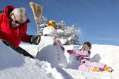 Little girl and grandfather making a snowman — Stock Photo