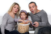 Parents with daughter watching TV and eating popcorn — Stock Photo