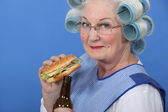 Granny eating a burger and drinking a beer — Stock Photo