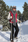 Woman walking through the snow with snow shoes — Stock Photo