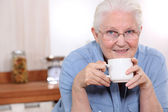 Elderly lady enjoying cup of tea in her kitchen — Stock Photo