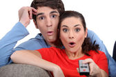 Shocked couple watching television — Stock Photo