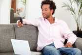Man sat at home with laptop and mobile — Stock Photo