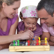 Family playing board game together — Stock Photo #9590181