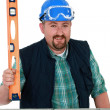 Chubby mason stood with spirit-level — Stockfoto