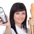 Womholding mobile phone and bread — Stock Photo #9591827