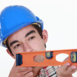 Stock Photo: Young carpenter using ruler