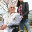 Pushing grandma in wheelchair — 图库照片