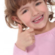 Smiling little girl giving the thumbs up — Stock Photo