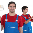 Two decorators with a roller and paint — Stock Photo #9595088