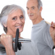 Grey-haired couple lifting weights — Stock Photo #9595289