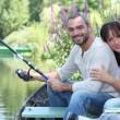 Couple sitting in a boat fishing — Stock Photo