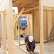 Stock Photo: Builder working on a wooden structure