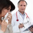 Stock Photo: Doctor and female patient with flu