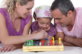 Family playing a board game together — Stock Photo