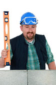 Chubby mason stood with spirit-level — Stock Photo