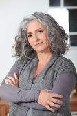 Grey haired woman stood in the kitchen with her arms folded — Stock Photo