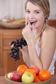 Woman eating grapes — Stock Photo