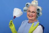 Elderly lady dusting — Stock Photo