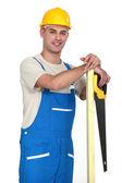 Feliz comerciante sosteniendo un tablón de madera y una sierra — Foto de Stock