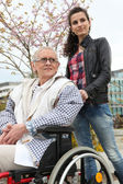 Pushing grandma in wheelchair — Stock Photo