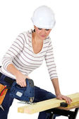Attractive young female joiner using sander machine — Stock Photo