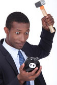 Insane man smashing open a piggy bank with a hammer — Stock Photo