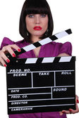 Woman holding up a clapperboard — Stock Photo