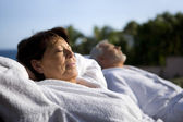 Couple laying outside in bathing robes — Stock Photo