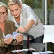 Stock Photo: Grandmother playing cards with granddaughter
