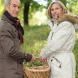 Couple walking through field with basket — Stock Photo #9607983