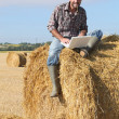 Farmer with laptop sitting on haystack — Stock Photo #9608321