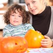 Woman carving pumpkins with her child — Stock Photo #9609304
