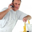 Stock Photo: Decorator making phone call whilst up ladder