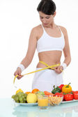 Pretty brunette doing sport and eating healthily — Stock Photo