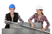 Female construction workers lifting a bar — Stock Photo
