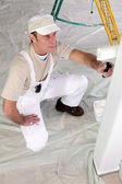Decorator repainting front room — Stock Photo