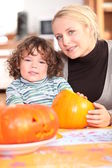 Woman carving pumpkins with her child — Stock Photo