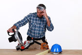 Craftsman looking at his new electric saw — Stock Photo