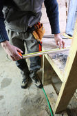 Carpenter measuring plank of wood — Zdjęcie stockowe