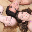 Friends lying on a beach - Stock fotografie