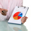 Stock Photo: Businessmshowing pie chart at meeting