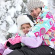Mother and daughter playing in the snow together — Stock Photo #9613728