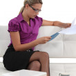 Blond businesswoman sat on a sofa reading through document — Stock Photo #9613742