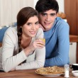 Stock Photo: Young couple in kitchen eating pancakes
